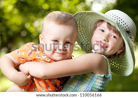 Girl holds in her arms her little brother