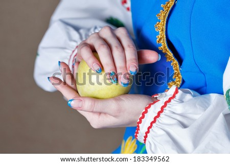 Girl holds in her hands with manicure ripe apple shot close up - stock photo