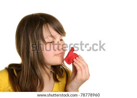 Girl holds petal of flower and smells isolated in white