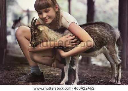 girl hugging a goat on a farm.