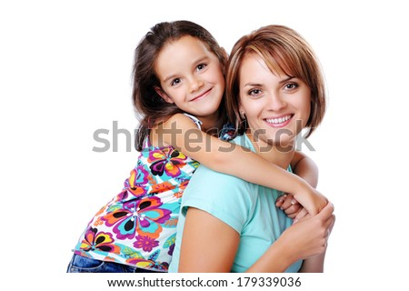 girl hugging happy mom from behind