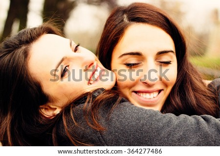 Girl hugging her best friend. In the park  - stock photo