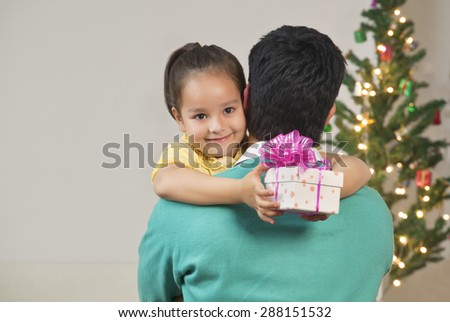 Girl hugging her dad while holding Christmas gift - stock photo