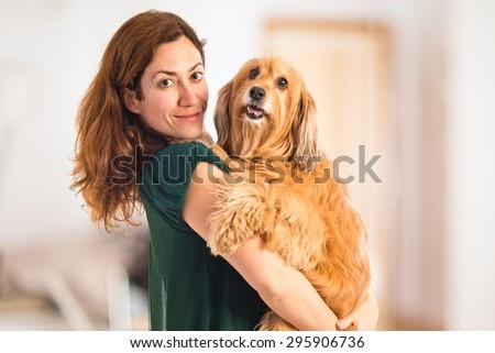 Girl hugging her dog inside house - stock photo