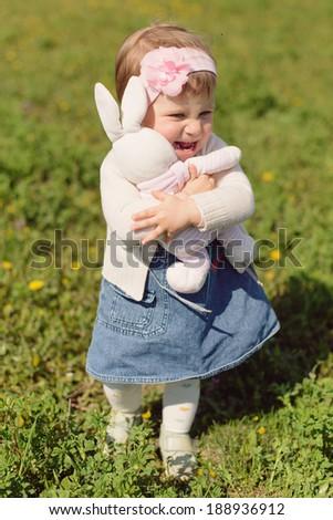 girl hugging her toy rabbit in meadow - stock photo