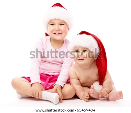 Girl hugs her little brother, both wearing red Christmas caps and smile, isolated over white - stock photo