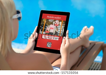 girl in a bathing suit lying on a sun lounger by the pool with a computer tablet with mobile wallet onlain shopping on the screen - stock photo