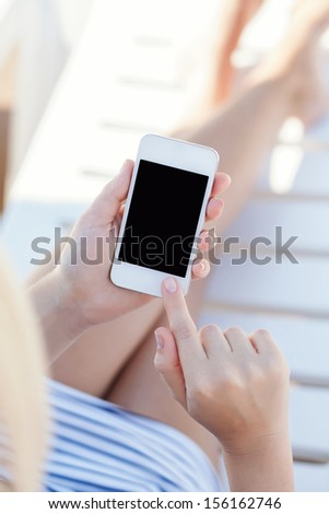girl in a bathing suit lying on a white chaise lounge with touch phone - stock photo