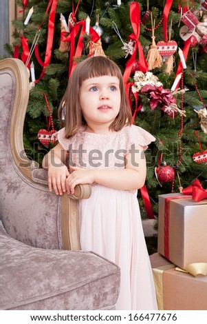 Girl in a beautiful pink dress stands near a Christmas fir-tree