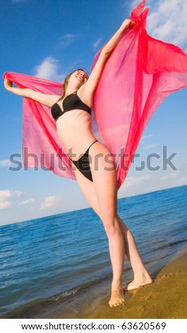 Girl in a black bathing suit on a background of blue sky