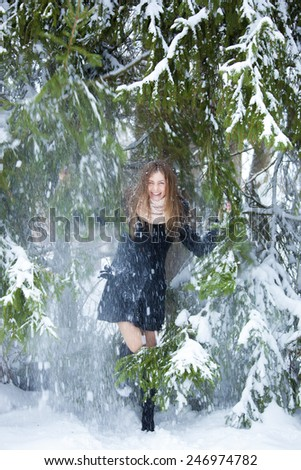 Girl in a black coat standing in a winter forest to under the Christmas tree which throws the snow - stock photo