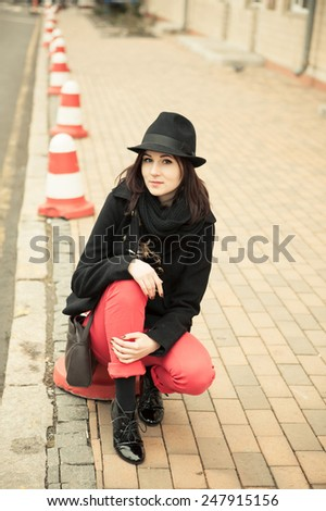 girl in a black hat sitting on the curb the outdoor - stock photo