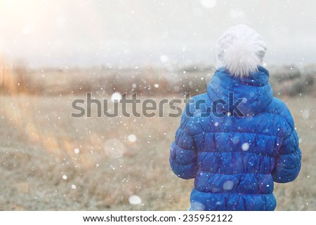 girl in a blue down jacket winter view from the back - stock photo
