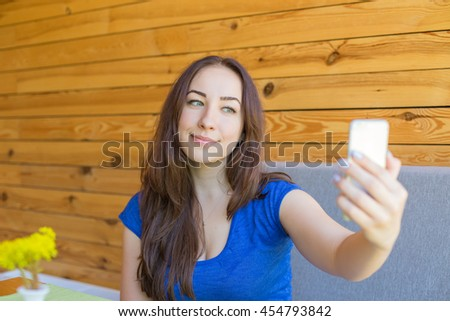 girl in a blue t-shirt makes selfie