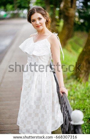 Girl in a bright dress posing in a green park