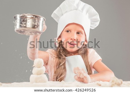 Girl in a cap and cook in an apron playing with flour and sieve - stock photo