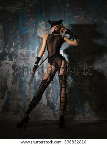 Girl in a cap, in beautiful lingerie with a whip stands near the wall. - stock photo