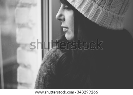 Girl in a cap looks out of the window. Black and white photo closeup. - stock photo