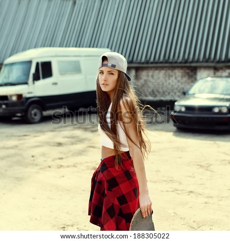 Girl in a cap on a sunny day comes with skateboard in hand