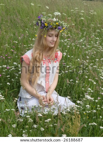 girl in a chaplet from meadow flowers and clothing of russian woman of XV age