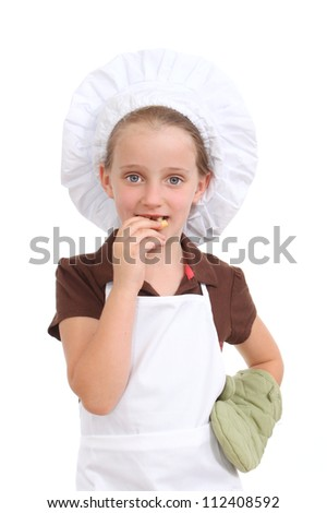 Girl in a chef's hat eating a cookie