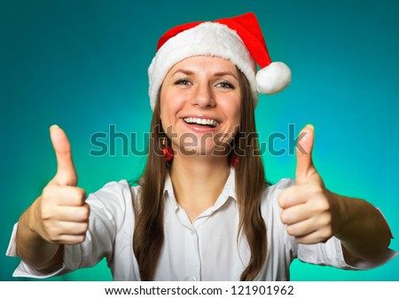 Girl in a Christmas hat blows off snowflakes on blue background