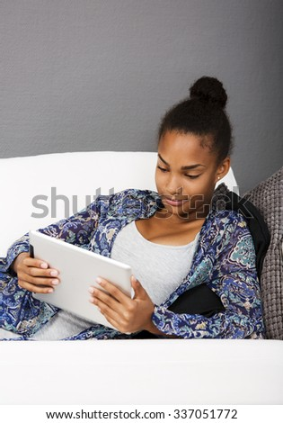 Girl in a couch with an electronic tablet in her hands. - stock photo