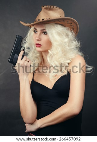 girl in a cowboy hat with a gun.An attractive cowgirl