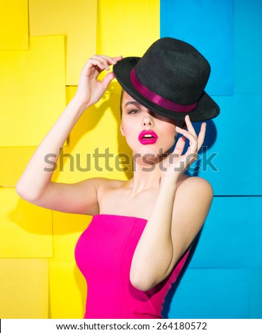 Girl in a crimson dress and black hat  - stock photo