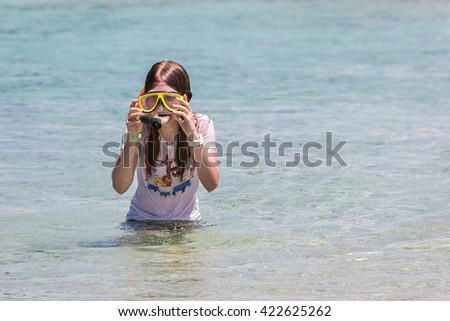 Girl in a diving mask preparing to dive into the clear sea