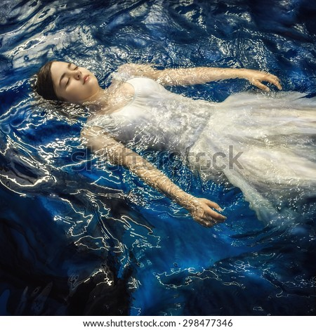 Girl in a dress in the water - stock photo