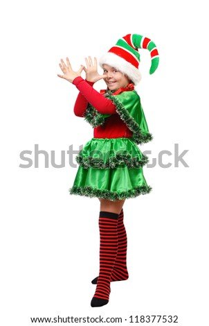 Girl in a dress of the Christmas elf shows teasing. Isolated on a white background - stock photo
