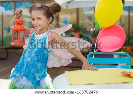 Girl in a fairy costume with a lantern in hand in a cafe - stock photo