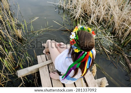 girl in a flower wreath on his head sitting on the bridge and wets feet in the river - stock photo