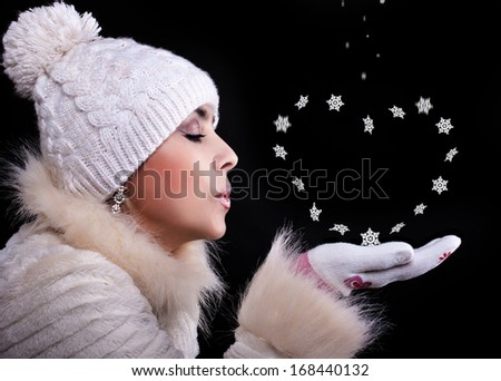 Girl in a fur coat, hat, and gloves on a black background blows away with the palms snowflakes - stock photo
