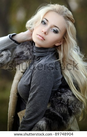girl in a fur coat in the autumn background - stock photo