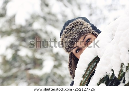 Girl in a fur hat, Pretty young woman with winter hat, outside portrait  - stock photo