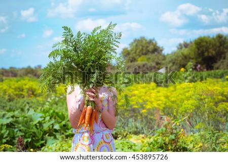 girl in a garden holding a carrot - stock photo