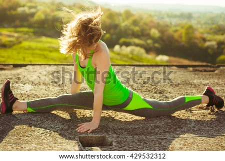 Girl in a green t-shirt is making front split with right leg forward