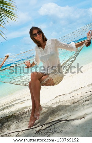 Girl in a hammock on the shores of the azure ocean (Maldives - Lhaviyani Atoll) - stock photo