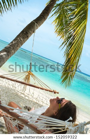 Girl in a hammock on the shores of the Indian ocean (Maldives - Lhaviyani Atoll) - stock photo
