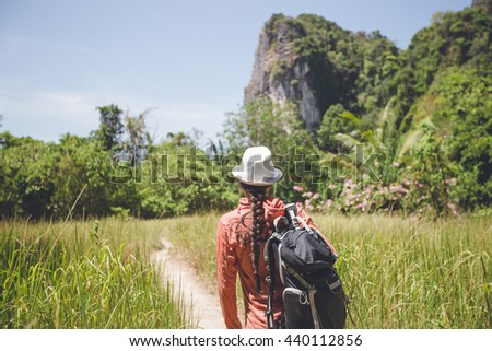 Girl in a hat and with a backpack walking along the trail in the jungle - stock photo