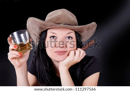 girl in a hat with a cigar and whiskey dark background - stock photo