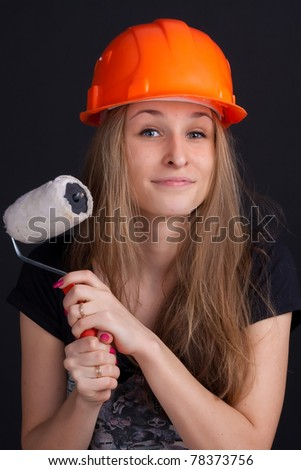 girl in a helmet with a roller to paint in his hand - stock photo