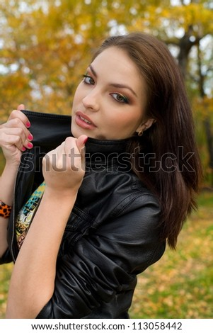 girl in a leather jacket on a background of autumn park