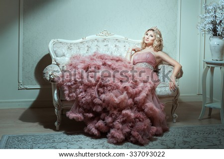 Girl in a magnificent dress sitting on the sofa. On her head a crown it fashionable. - stock photo