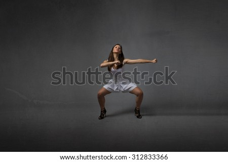 girl in a martial arts pose, dark background - stock photo