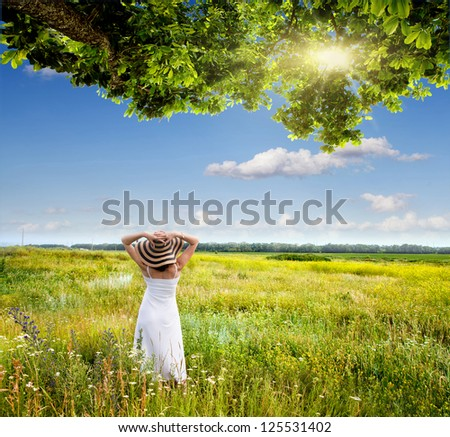 girl in a meadow under a tree