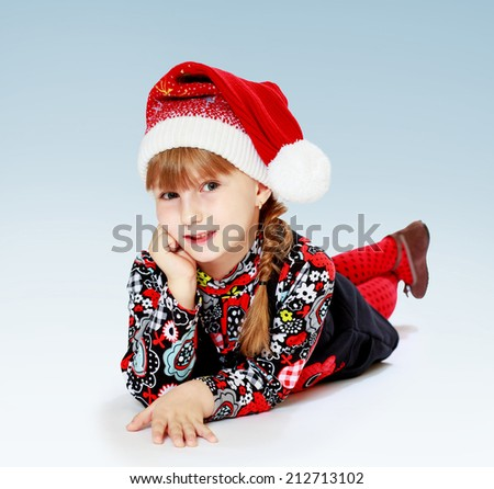 girl in a New Year's cap lying on the floor.The concept of development of the child younger years. - stock photo