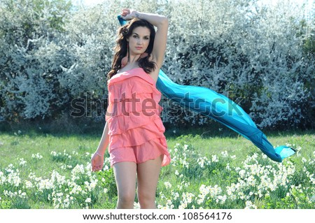 girl in a pink dress plays with a blue ribbon in a field of daisies - stock photo